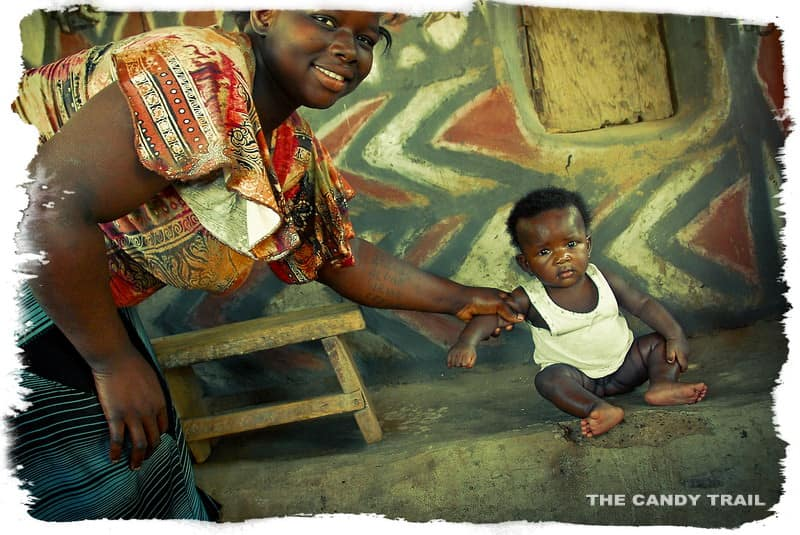 Woman and baby at painted houses of Ghana in Sirigu village.
