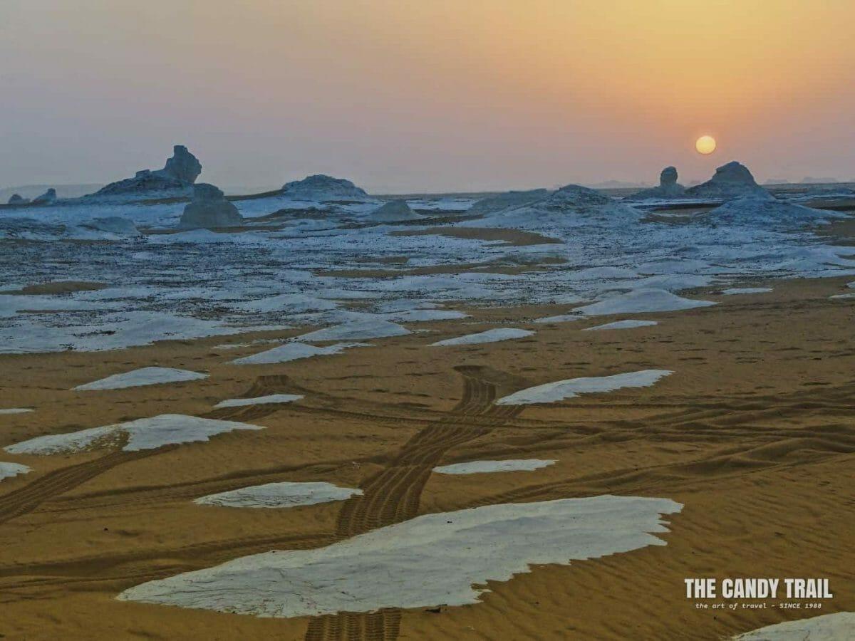 sunset over strange white desert formations on tour in egypt