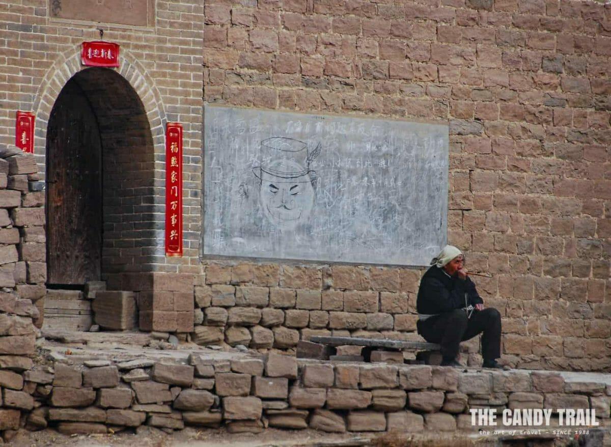 man smoking pipe lijiashan village china