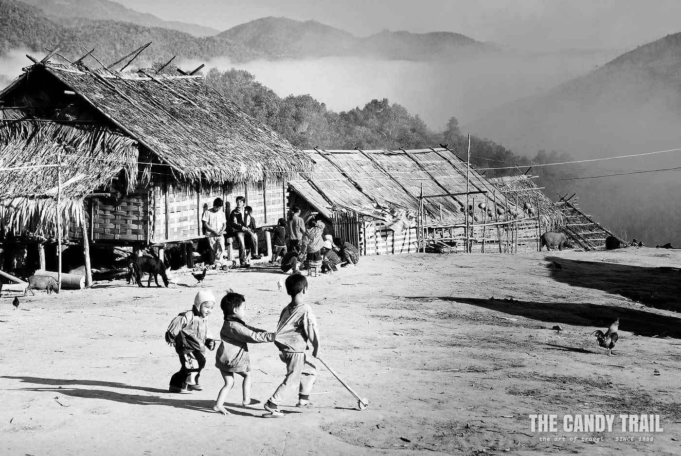 black and white kids playing in akha hill tribe village laos