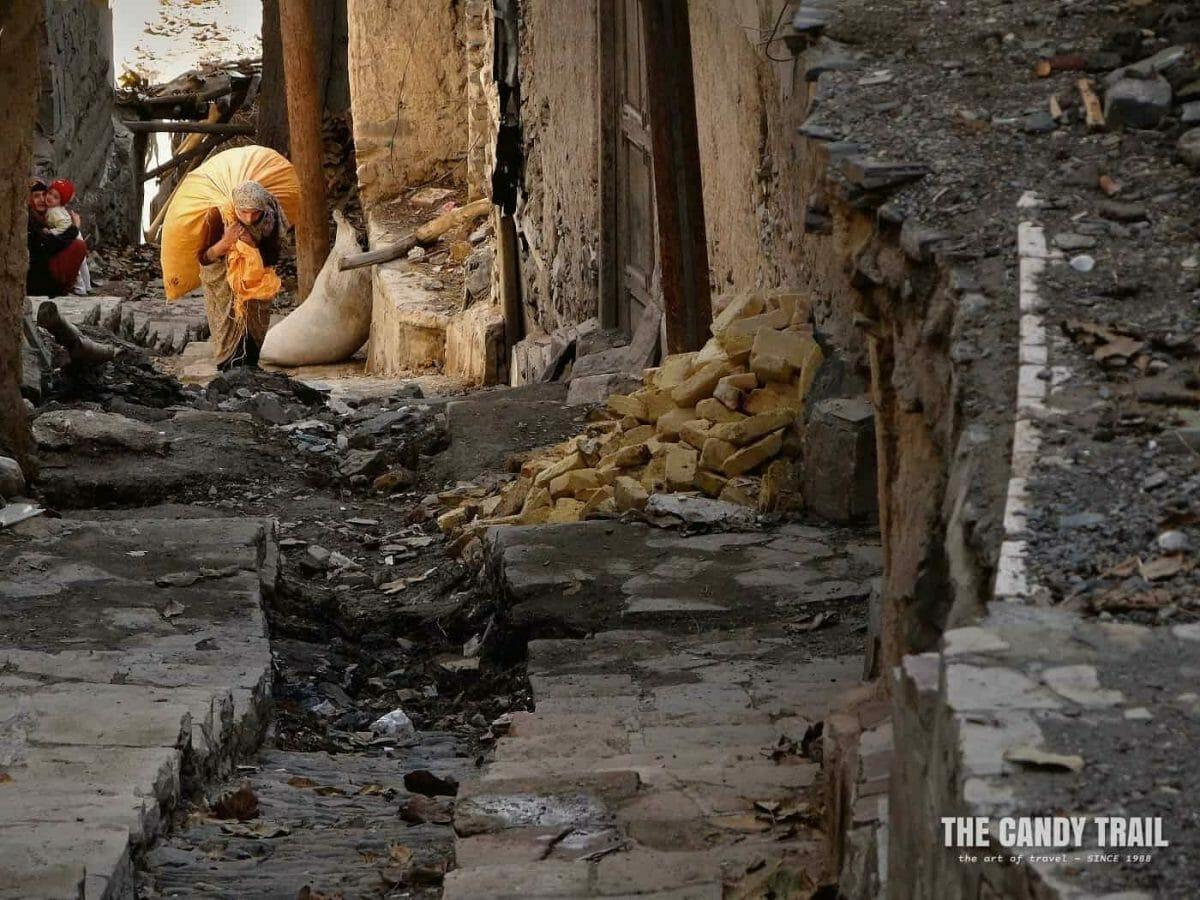 Women lugs up a huge bag steep, stepped lanes of Kang village Iran
